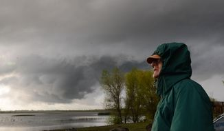 Larry Crisman watches clouds circle around the sky over the Llano Seco Unit of the Sacramento River Wildlife Refuge as a severe storm brought funnel clouds and a report of a tornado touchdown Wednesday, March 26, 2014 in Dayton, Calif.  (AP Photo/The Chico Enterprise-Record, Jason Halley)