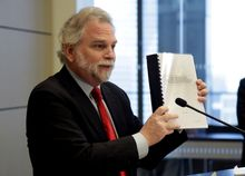 Attorney Randy Mastro holds up a copy of his report during a news conference Thursday, March 27, 2014, in New York.  Mastro, with the law firm hired by New Jersey Gov. Chris Christie, said Thursday that the governor was not involved in a plot to create gridlock near a major bridge as part of a political retribution scheme. (AP Photo/Richard Drew)