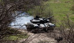 A tank maneuvers near a former Ukrainian military base in Perevalne, outside Simferopol, Crimea, March 27, 2014. Russia last week completed the annexation of Crimea following a referendum in which an overwhelming number of residents voted to break off from Ukraine and join Russia. The vote, rejected by Ukraine and the West, was hastily called after Russian forces had overtaken the peninsula.(AP Photo/Pavel Golovkin)