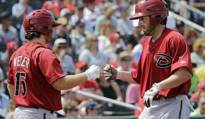 Arizona Diamondbacks' Nick Evans, right, is greeted by teammate Garrett Weber (15) after hitting a solo home run off Cincinnati Reds starting pitcher Tony Cingrani in the fourth inning of a spring exhibition baseball game on Thursday, March 27, 2014, in Goodyear, Ariz. (AP Photo/Mark Duncan)