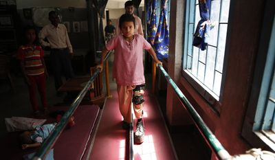 A polio-affected boy Manish, 8, learns to walk with his orthoses after a surgery at a physical rehabilitation center in New Delhi, India Thursday, March 27, 2014. The World Health Organization has formally declared India polio-free, with no new case of the disease detected in the country in the past three years. (AP Photo /Manish Swarup)