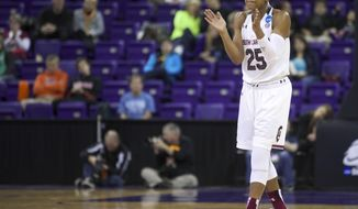 FILE - In this March 25, 2014 file photo, many empty seats are seen as South Carolina's Tiffany Mitchell cheers her teammates during the second half of a second-round game against Oregon State in the NCAA women's college basketball tournament in Seattle. Attendance is down for the opening two rounds of the women's basketball tournament. The NCAA hopes that with three schools hosting the regional rounds more fans will turn out. (AP Photo/Stephen Brashear, File)
