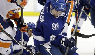 Tampa Bay Lightning center Tyler Johnson (9) gets off a shot from his knees in front of New York Islanders defenseman Thomas Hickey (14) and center Casey Cizikas (53) during the second period of an NHL hockey game Thursday, March 27, 2014, in Tampa, Fla. (AP Photo/Chris O'Meara)
