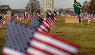 Navy Veterans Cmrd. Jeff Hensley and his girlfriend Petty Officer 1st Class Colleen Ryan of Frisco, Texas, embrace and cry together after learning that a former shipmen serving with Ryan had committed suicide the night before, Washington, D.C., Thursday, March 27, 2014. Veterans and supporters place American flags on the National Mall to represent each of the 1,892 veterans and service members who have died by suicide this year. (Andrew Harnik/The Washington Times)