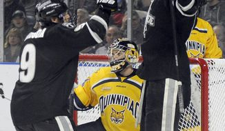 Quinnipiac goaltender Michael Garteig, center, reacts after being scored on by Providence during the first period of a game in the men's NCAA East Regional hockey tournament on Friday, March 28, 2014, in Bridgeport, Conn. (AP Photo/Fred Beckham)