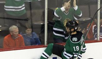North Dakota forward Rocco Grimaldi (19) celebrates after scoring a goal against Wisconsin in the second period of a regional semifinal of the NCAA college hockey tournament on Friday, March 28, 2014, in Cincinnati. North Dakota forward Stephane Pattyn (28) looks on. (AP Photo/Al Behrman)