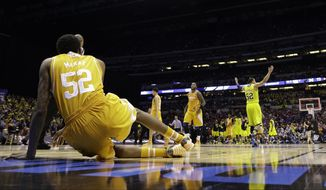 Michigan's Jordan Morgan, right, raises his arms as Tennessee's Jordan McRae gets off the floor after an NCAA Midwest Regional semifinal college basketball tournament game Friday, March 28, 2014, in Indianapolis. Michigan won 73-71.(AP Photo/David J. Phillip)