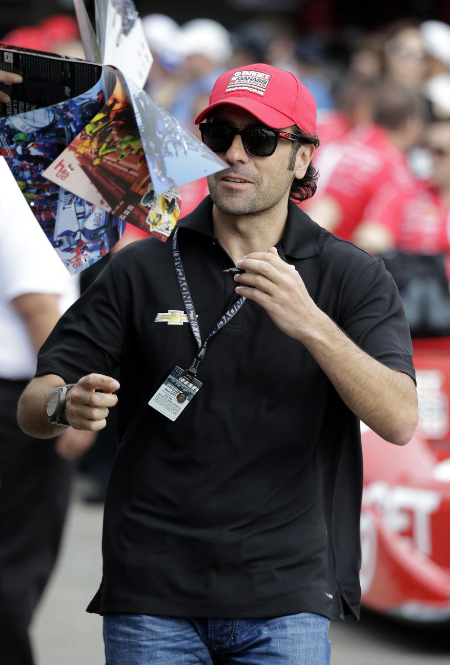 Former driver Dario Franchitti, of Scotland, signs autographs before practice for the IndyCar Firestone Grand Prix of St. Petersburg auto race Friday, March 28, 2014, in St. Petersburg, Fla. Franchitti was forced to retire from driving after a crash on Oct. 6, 2013 in Houston.  He is now a driving coach for Chip Ganassi racing. (AP Photo/Chris O'Meara)