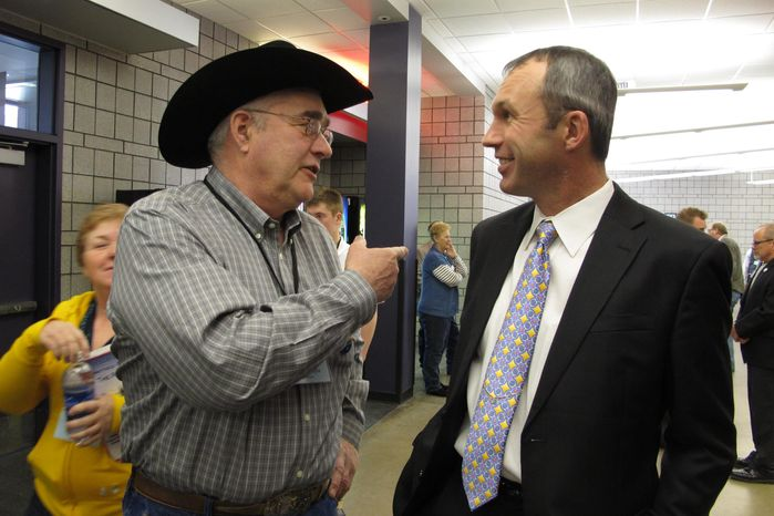 North Dakota Democratic convention delegate Dean Meyer, left, talks with the party's nominee for state agriculture commissioner, Ryan Taylor, during events Friday, March 28, 2014, in Fargo, N.D. (AP P