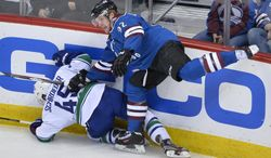 Colorado Avalanche left wing Gabriel Landeskog (92), from Sweden, boards Vancouver Canucks center Jordan Schroeder (45) during the first period of an NHL hockey game on Thursday, March 27, 2014, in Denver. (AP Photo/Jack Dempsey)