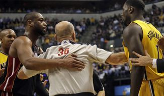 In this Wednesday, March 26, 2014 photo, Miami Heat guard Dwyane Wade, left, and Indiana Pacers guard Lance Stephenson, right, are separated by official David Jones during the second half of an NBA basketball game in Indianapolis. The Pacers won 84-83. Before the game, the teams chided one another with dueling comments. Afterward, nobody was ready to make up. And in between, the action got downright nasty. (AP Photo/AJ Mast)