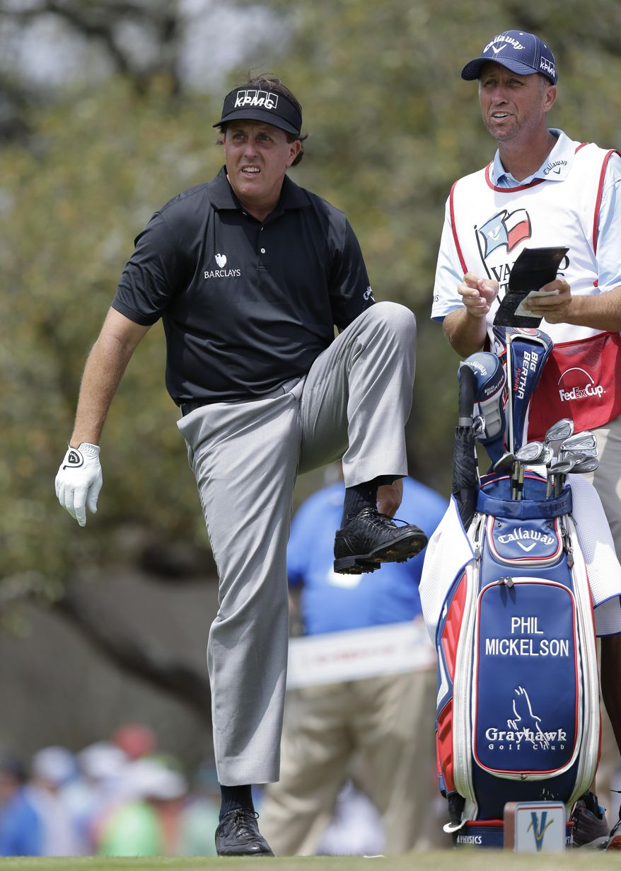 """Phil Mickelson, left, with his caddie, Jim """"Bones"""" Mackay, waits to hit on the second hole during the second round of the Texas Open golf tournament, Friday, March 28, 2014, in San Antonio. (AP Photo/Eric Gay)"""