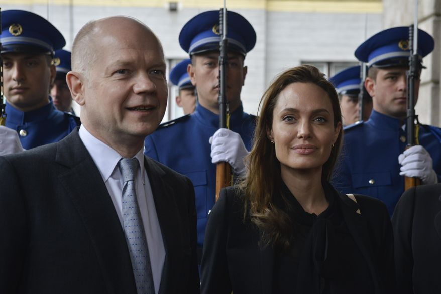 UNHCR goodwill ambassador Angelina Jolie and British Foreign Secretary William Hague pose for photographers upon their arrival for a meeting with the Bosnian Presidency in Sarajevo, Bosnia, on Friday March 28, 2014. British Foreign Secretary William Hague and Hollywood star Angelina Jolie addressed a conference organized in Sarajevo by Bosnia's Defense Ministry on sexual violence in conflict. (AP Photo/Sulejman Omerbasic)