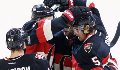 Ottawa Senators' Cory Ceci (5) celebrates his goal against the Chicago Blackhawks with teammates Patrick Wiercioch (46) and Mark Stone (61) during first-period NHL hockey game action in Ottawa, Ontario, Friday, March 28, 2014. (AP Photo/The Canadian Press, Fred Chartrand)