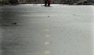 A search and rescue worker carrying a probe wades through water covering Washington Highway 530 Thursday, March 27, 2014, on the eastern edge of the massive mudslide that struck Saturday near Darrington, Wash. (AP Photo/Ted S. Warren, Pool)
