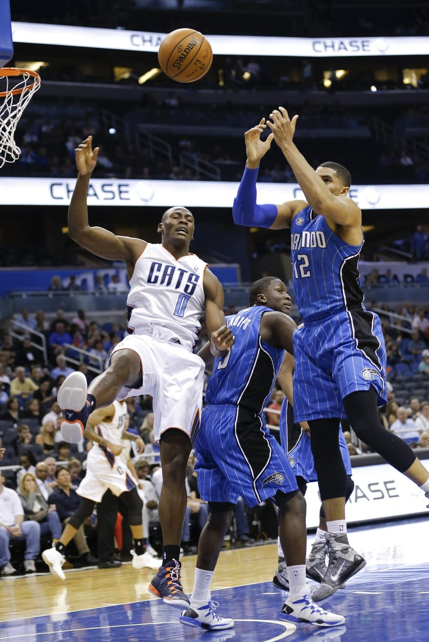 Charlotte Bobcats' Bismack Biyombo (0) and Orlando Magic's Tobias Harris (12) go after a rebound during the first half of an NBA basketball game in Orlando, Fla., Friday, March 28, 2014. (AP Photo/John Raoux)