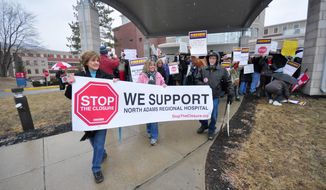 More than 100 demonstrators stand outside to protest the closing of North Adams Regional Hospital, on Friday, March 28, 2014, in North Adams, Mass. The hospital announced the closure of the community hospital, on Tuesday. (AP Photo/The Berkshire Eagle, Gillian Jones)