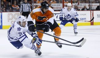 Philadelphia Flyers' Zac Rinaldo, center, shoves Toronto Maple Leafs' David Clarkson off the puck during the first period of an NHL hockey game, Friday, March 28, 2014, in Philadelphia. (AP Photo/Matt Slocum)