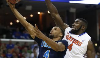 UCLA guard Norman Powell (4) shoots against Florida center Patric Young (4) during the first half in a regional semifinal game at the NCAA college basketball tournament, Thursday, March 27, 2014, in Memphis, Tenn. (AP Photo/John Bazemore)