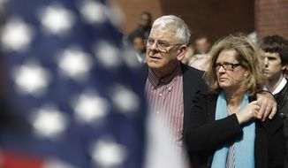 The mother and stepfather of Boston firefighter Michael R. Kennedy hold each other during a Boston Fire Department flag raising ceremony in honor of the fallen firefighters Kennedy and Lt. Edward J. Walsh on City Hall Plaza in Boston, Friday, March 28, 2014. Kennedy and Walsh were killed Wednesday, March 26, 2014 when they were trapped in the basement of a brownstone during a nine-alarm blaze. (AP Photo/Stephan Savoia)