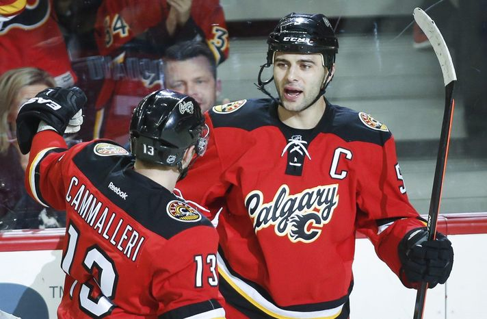Calgary Flames' Mark Giordano, right, celebrates his goal with teammate Mike Cammalleri during the first period of an NHL hockey game against the New York Rangers in Calgary, Alberta, Friday, March 28, 2014. (AP Photo/The Canadian Press, Jeff McIntosh)