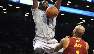 Brooklyn Nets' Andray Blatche (0) dunks in front of Cleveland Cavaliers' Jarrett Jack (1) during the first half of an NBA basketball game Friday, March 28, 2014, in New York. (AP Photo/Kathy Kmonicek)