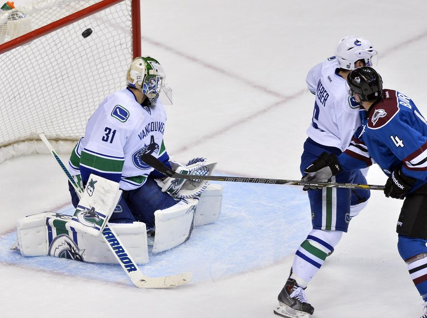 Vancouver Canucks goalie Eddie Lack (31), from Sweden, allows an overtime goal by Colorado Avalanche defenseman Tyson Barrie (4), as Canucks defenseman Yannick Weber (6), from Switzerland, helps on defense during an NHL hockey game, Thursday, March 27, 2014, in Denver. Colorado won 3-2. (AP Photo/Jack Dempsey)