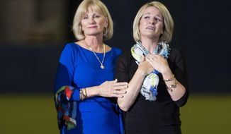 Sandy Carter, left, wife of former Montreal Expos Gary Carter, and her daughter Kimmy acknowledge applauds from the crowd during a ceremony prior to a pre-season game between the Toronto Blue Jays and the New York Mets Friday, March 28, 2014 in Montreal.  (AP Photo/The Canadian Press, Paul Chiasson)