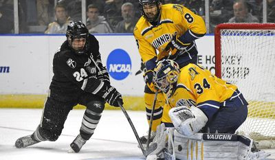 Providence's Noel Acciari's shot is stopped by Quinnipiac goaltender Michael Garteig (34) as Alex Barron (8) looks on during the first period during a game in the men's NCAA East Regional hockey tournament Friday, March 28, 2014, in Bridgeport, Conn. (AP Photo/Fred Beckham)