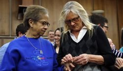 FILE - In this March 22, 2014 file photo Pennye Mattson, right, places a wedding ring on Sherrie Tyler, left, while being married in a group by the Oakland County Clerk in Pontiac, Mich., after a federal judge has struck down Michigan's ban on gay marriage. Attorney General Eric Holder on Friday, March 28, 2014 extended federal recognition to the marriages of about 300 same-sex couples that took place in Michigan before a federal appeals court put those unions on hold. (AP Photo/Paul Sancya, File)