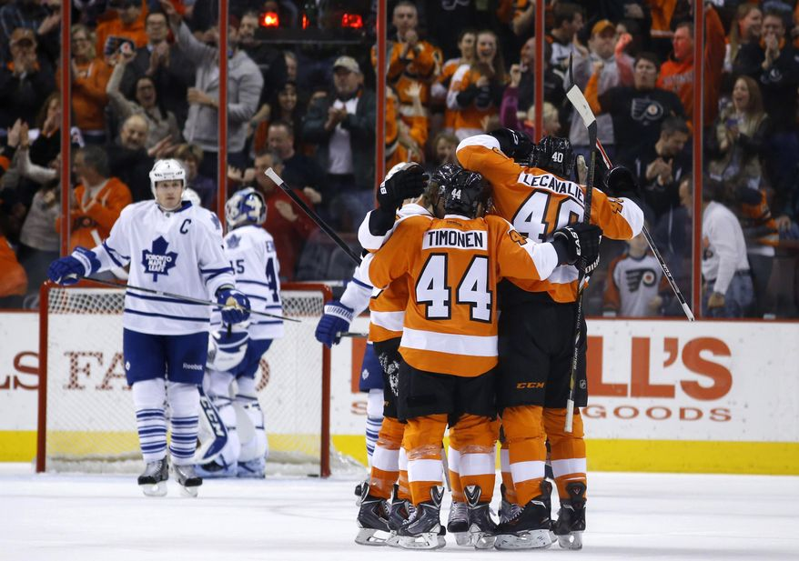 Philadelphia Flyers' Kimmo Timonen (44), of Finland, and Vincent Lecavalier (40) celebrate with teammates after Lecavalier's goal during the first period of an NHL hockey game against the Toronto Maple Leafs, Friday, March 28, 2014, in Philadelphia. (AP Photo/Matt Slocum)