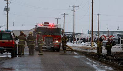 Fresh firefighters arrive at the scene of an overnight fire at WL Plastics on Thursday morning, March 27, 2014 west of Casper, Wyo.  (AP Photo/The Casper Star-Tribune, Alan Rogers)
