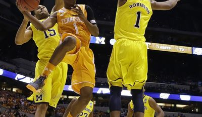 Tennessee's Josh Richardson passes around Michigan's Glenn Robinson III (1) and Jon Horford (15) during the first half of an NCAA Midwest Regional semifinal college basketball tournament game Friday, March 28, 2014, in Indianapolis. (AP Photo/Michael Conroy)