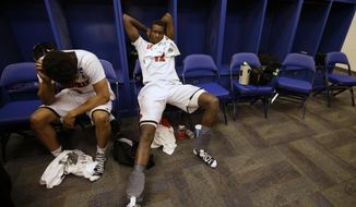 Louisville's Anton Gill and Mangok Mathiang (12) pause in the locker room after an NCAA Midwest Regional semifinal college basketball tournament game against the Kentucky Saturday, March 29, 2014, in Indianapolis. Kentucky won 74-69. (AP Photo/David J. Phillip)