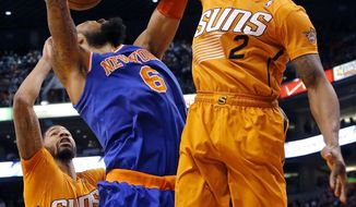 New York Knicks' Tyson Chandler (6) has his shot blocked by Phoenix Suns'  Eric Bledsoe (2) during the first half of an NBA basketball game, Friday, March 28, 2014, in Phoenix. (AP Photo/Matt York)