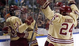 Boston College's Johnny Gaudreau (13) celebrates his goal against Denver with teammates Teddy Doherty (4) and Bill Arnold (24) in the first period of an NCAA Northeast Regional hockey game in Worcester, Mass., Saturday, March 29, 2014. (AP Photo/Elise Amendola)