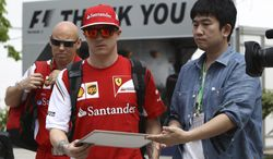 Ferrari driver Kimi Raikkonen, center, of Finland signs prepares to sign his autograph for a fan as he arrives at the paddock for the third practice session and qualifying session for Sunday's Malaysian Formula One Grand Prix at Sepang International Circuit in Sepang, Malaysia, Saturday, March 29, 2014. (AP Photo/Lai Seng Sin)