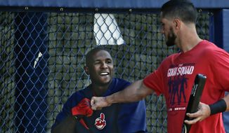 Cleveland Indians catcher Yan Gomes,  right, knocks knuckles with right fielder Nyjer Morgan before a spring exhibition baseball game on Friday, March 28, 2014, in San Diego. (AP Photo/Lenny Ignelzi)