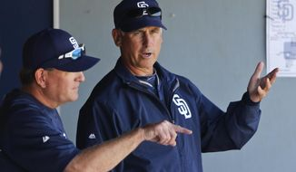 San Diego Padres manager Bud Black, right, talks with pitching coach Darren Balsley during a spring  training exhibition baseball game against the Cleveland Indians, Saturday, March 29, 2014, in San Diego. (AP Photo/Lenny Ignelzi)