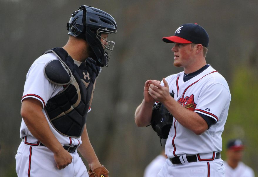 Atlanta Braves pitcher Craig Kimbrell, right, talks to catcher Evan Gattis during the fourth inning of their exhibition baseball game against the team's minor league Future Stars Saturday, March 29, 2014, in Rome, Ga. (AP Photo/David Tulis)