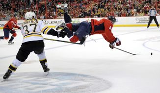 Washington Capitals right wing Alex Ovechkin (8), of Russia, goes airborne after he was tripped up by Boston Bruins center Patrice Bergeron (37) during the first period of an NHL hockey game, Saturday, March 29, 2014, in Washington. (AP Photo/Nick Wass)
