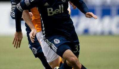 Vancouver Whitecaps' Steven Beitashour, right, and Russell Teibert, left, and Houston Dynamo's Andrew Driver, of England, chase down the ball during the second half of an MLS soccer game in Vancouver, British Columbia, Saturday, March 29, 2014. (AP Photo/The Canadian Press, Darryl Dyck)