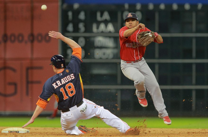 Rojos del Aguila de Veracruz shortstop Alejandro Rivero, right, watches his double-play throw to first baseman Sharnol Adriana as Houston Astros' Marc Krauss is out at second base in the seventh inning of a spring exhibition baseball game on Saturday, March 29, 2014, in Houston. (AP Photo/Richard Carson)