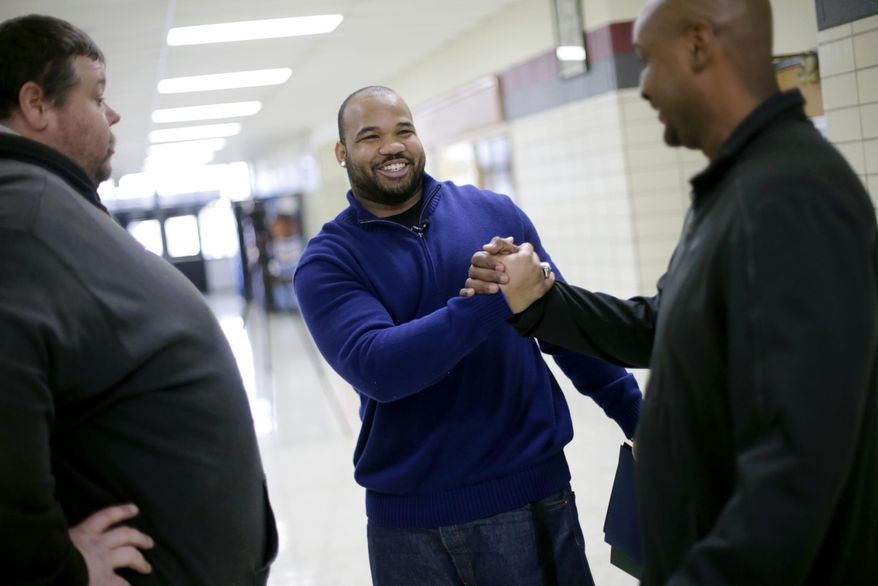 In this photo taken on Tuesday, March 25, 2014, University of Tulsa student Shawn Jackson, center, greets coaches Danny Clark, right, and Michael Davis Sr., following a ceremony that honored his achievements at his alma mater, McLain High School for Science and Technology in Tulsa, Okla. Jackson, who was named Conference USA's defensive player of the year while playing at Tulsa, played football when he was a student at McLain and was honored during an assembly for students. (AP Photo/Tulsa World,  John Clanton)  ONLINE OUT; KOTV OUT; KJRH OUT; KTUL OUT; KOKI OUT; KQCW OUT; KDOR OUT; TULSA OUT; TULSA ONLINE OUT