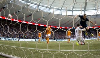 Vancouver Whitecaps' Jordan Harvey, right, scores a goal against Houston Dynamo goalkeeper Tally Hall during the first half of an MLS soccer game in Vancouver, British Columbia, on Saturday, March 29, 2014. (AP Photo/The Canadian Press, Darryl Dyck)