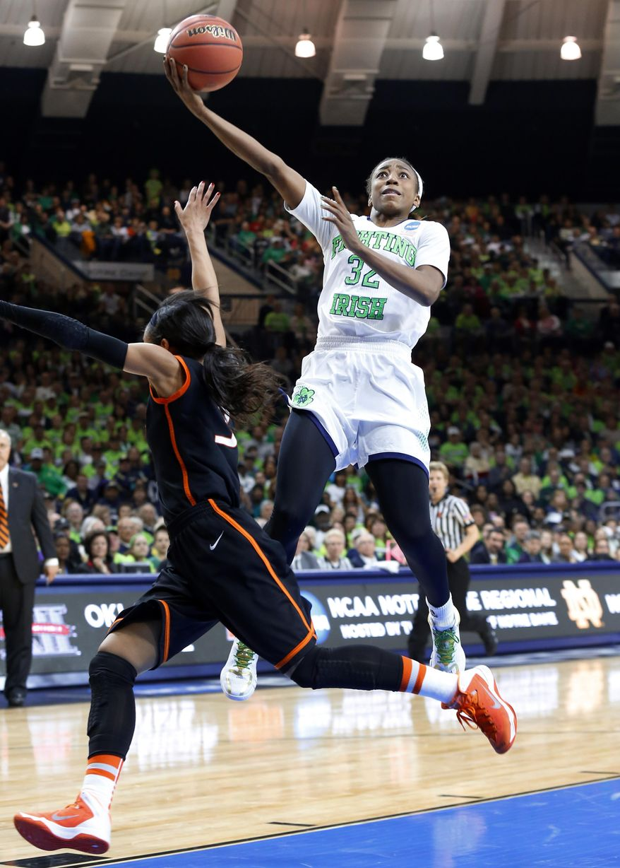 Notre Dame guard Jewell Loyd (32) shoots as Oklahoma State guard Tiffany Bias (3) defends during the first half of a regional semifinal in the NCAA college basketball tournament at the Purcell Pavilion in South Bend, Ind., Saturday, March 29, 2014. (AP Photo/Paul Sancya)