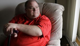 In this Thursday, March 27, 2014 photo, Patrick McClellan looks out the window of his home in Bloomington, Minn. McClellan uses a marijuana vaporizer to control muscle spasms caused by mitochondrial myopathy. (AP Photo/Ann Heisenfelt)