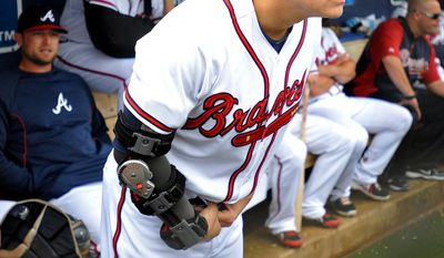 Atlanta Braves pitcher Kris Medlen wears an elbow brace on his right arm after season-ending Tommy John surgery as he waits during a rain delay in their exhibition baseball game against the team's minor league Future Stars Saturday, March 29, 2014, in Rome, Ga. (AP Photo/David Tulis)