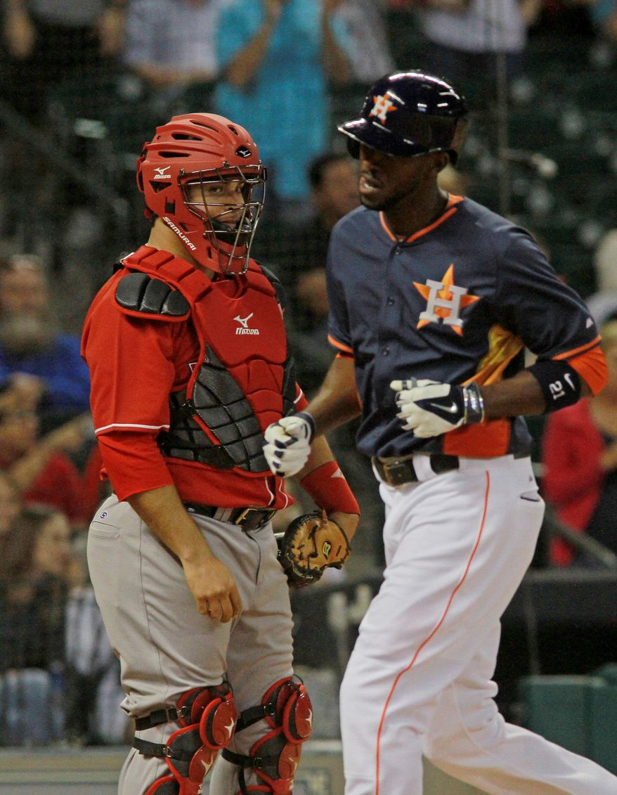 Rojos del Aguila de Veracruz catcher Humberto Sosa, left, watches as Houston Astros' Dexter Fowler crossed the plate after a solo home run in the fourth inning in a spring exhibition baseball game on Saturday, March 29, 2014, in Houston. (AP Photo/Richard Carson)