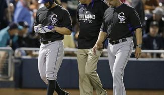 Colorado Rockies starting pitcher Tyler Chatwood leaves the field with trainer Keith Dugger and manager Walt Weiss after getting injured running for a triple during the third inning of an exhibition baseball game against the Seattle Mariners on Friday, March 28, 2014, in Peoria, Ariz. (AP Photo/Darron Cummings)